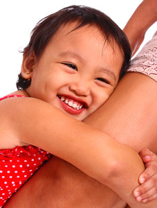 Happy Smiling Girl Hugging Her Mother's Leg With Love